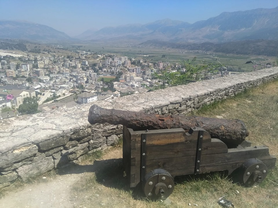 A cannon at the top of Gjirokaster fortress in Albania with the Old Town below and mountains behind