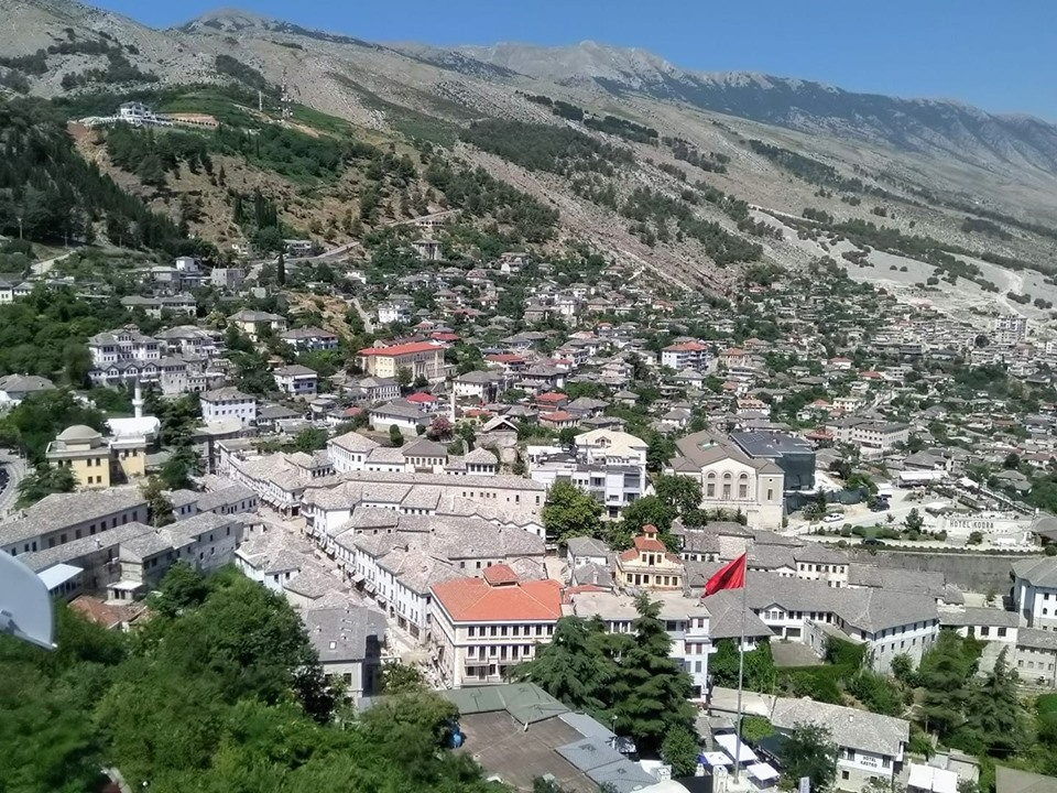 The view of grey stone rooves of Gjirokaster Old Town with mountains behind from Gjirokaster fortress, Albania