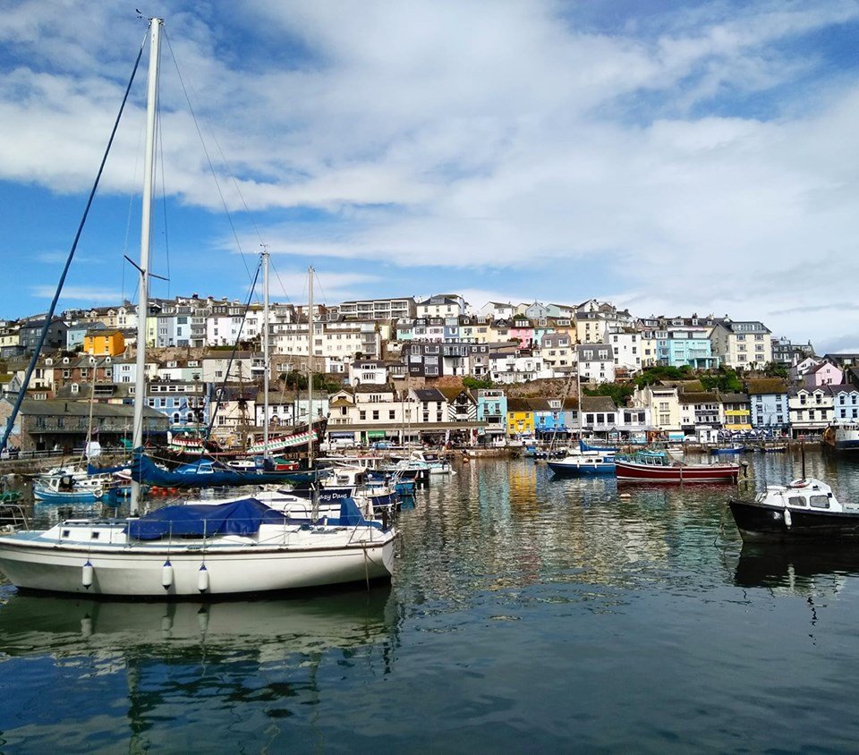 Fishing boats in the harbour with brightly coloured houses on the hill behind in Brixham, England
