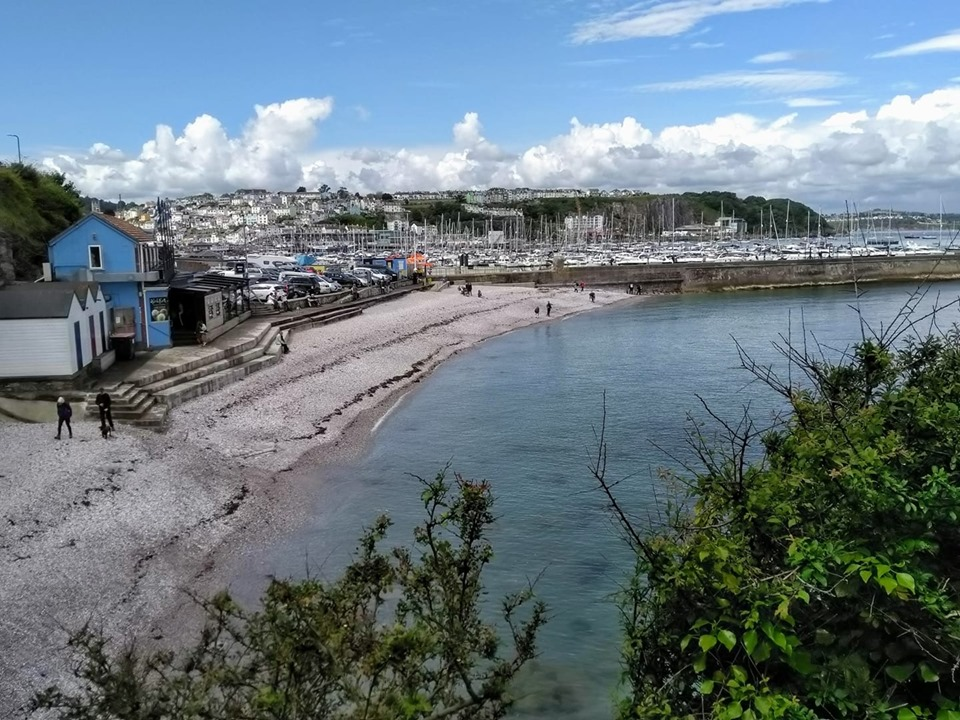 The pebbly beach of the breakwater at Brixham with the harbour and town behind