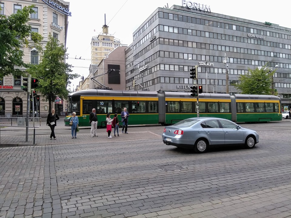 a Yellow and green tram in front of city buildings in Helsinki