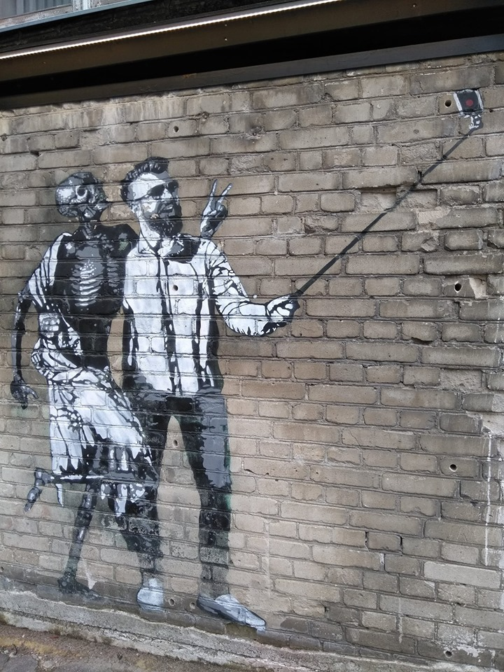Street art depicting a man taking a selfie with a skeleton