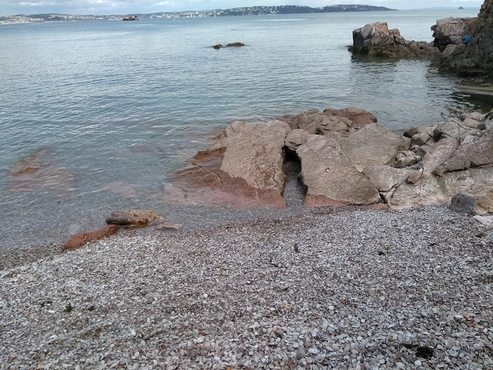 A rocky cove on the pebbly beach at the breakwater in Brixham