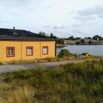 A yellow house by the sea with the fortress behind on Suomenlinna island in Helsinki