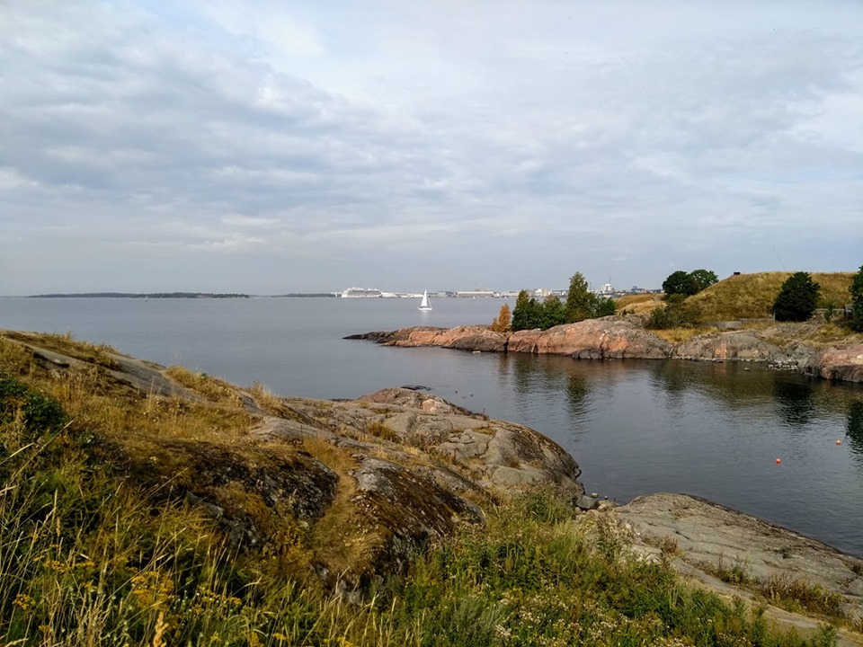 The sea and rocks from Suomenlinna, with a sailing boat in the distance