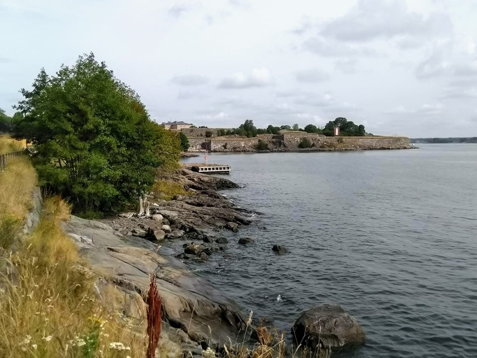 The rocky shore leading into the sea with the Suomenlinna fortress in the background