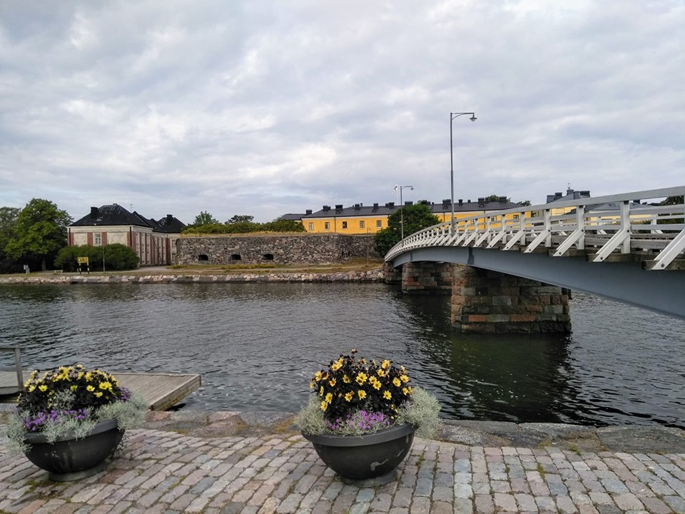 A bridge over the water and some flowerpots and yellow houses at Suomenlinna