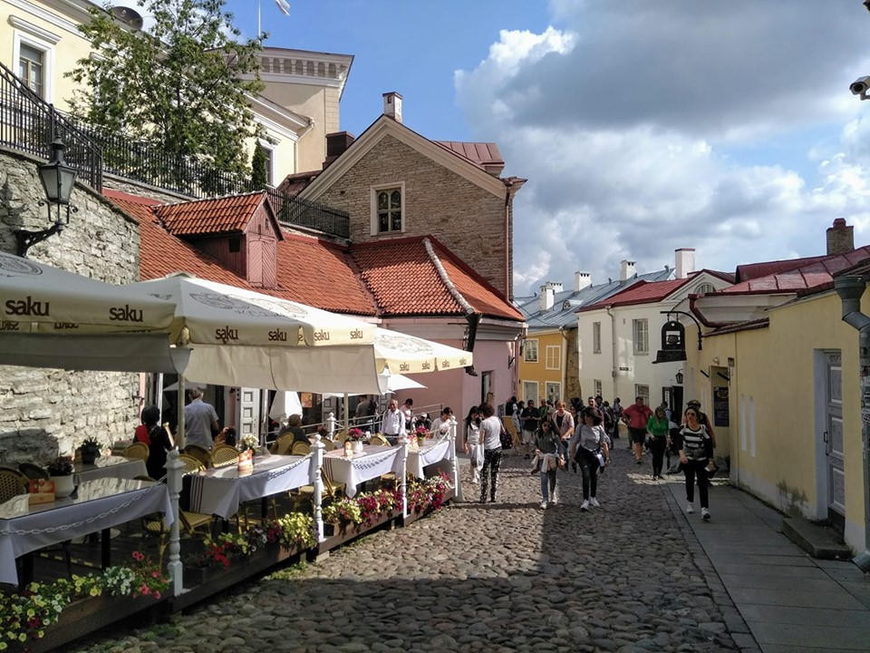 A cobbled street lined with cafe tables and brightly coloured buildings in Tallinn's Old Town