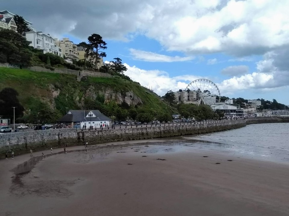 The beach at Torquay with cliffs and a big wheel behind it