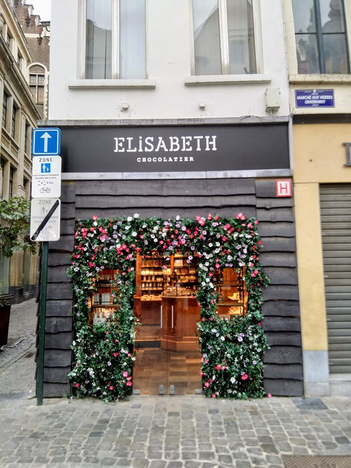 A chocolatier in Brussels with flowers and ivy decorating the doorway