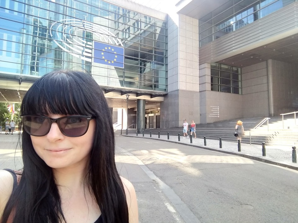 Rachel (young woman with long black hair and wearing sunglasses) taking a selfie in front of the European Parliament in Brussels