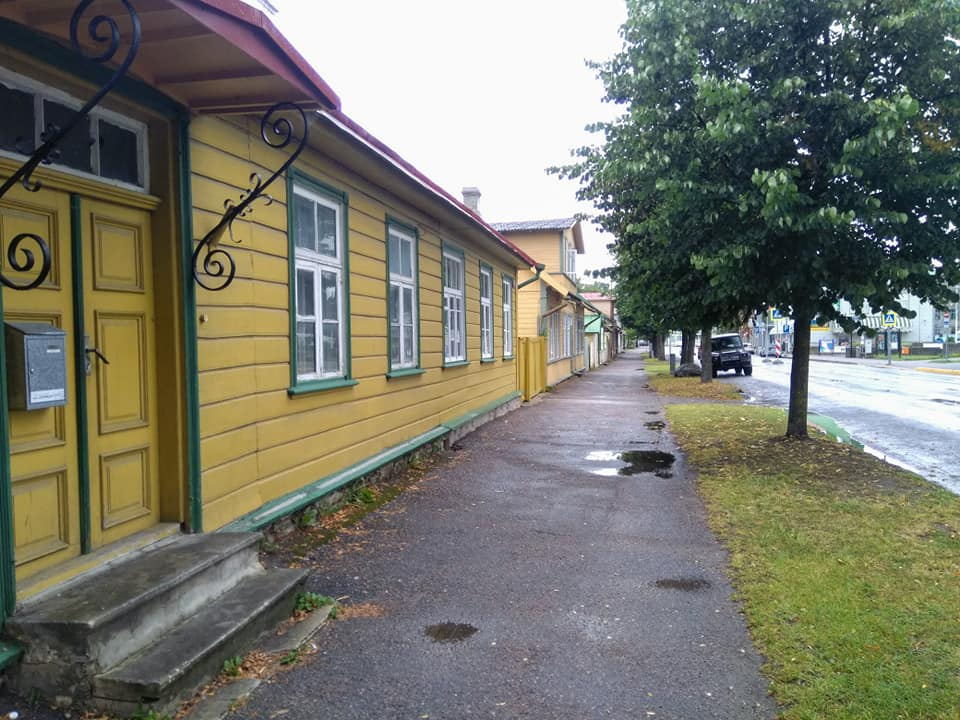Yellow wooden houses on a wet street on the way into the Old Town in Haapsalu, Estonia
