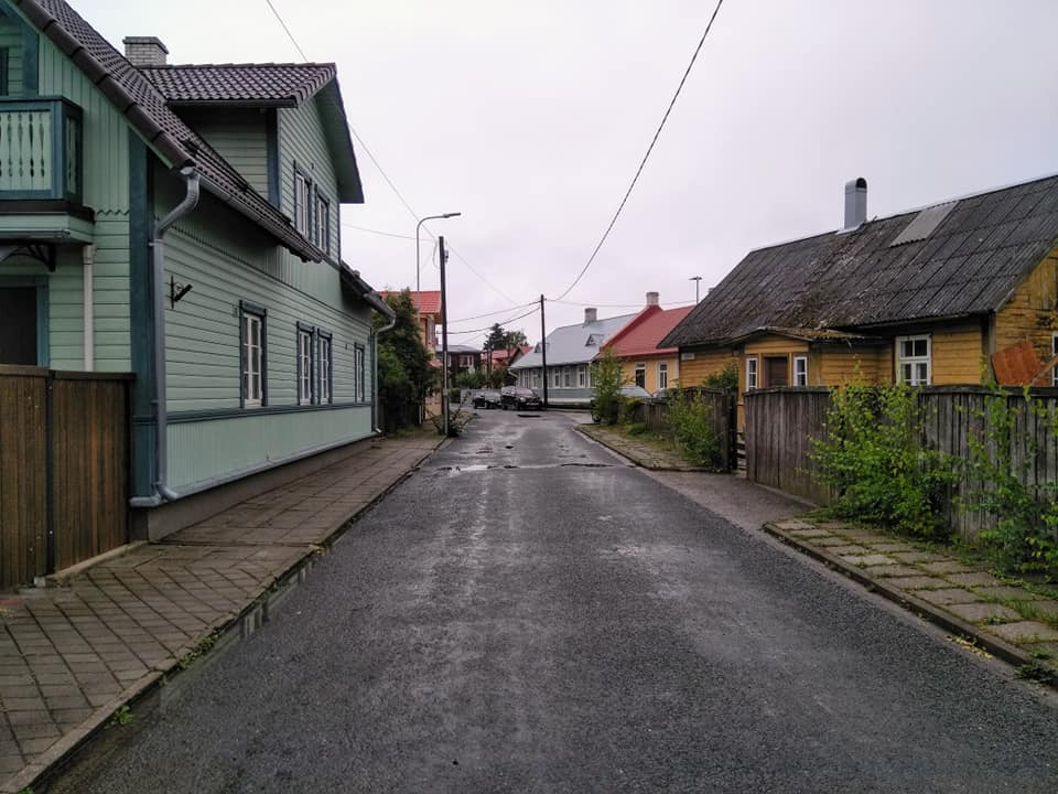 Brightly coloured wooden house on a wet street on the way into the Old Town in Haapsalu, Estonia