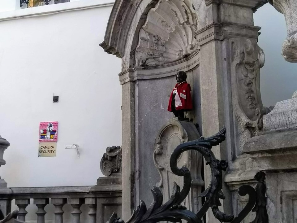 The Manneken Pis, a statue of a little boy urinating into a fountain, dressed in a little red coat