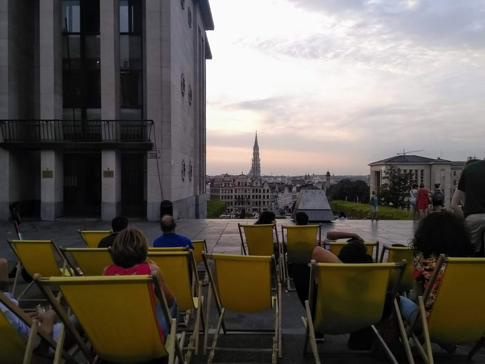The sun setting over Brussels as viewed from the Mont des Arts with people sitting in yellow deckchairs