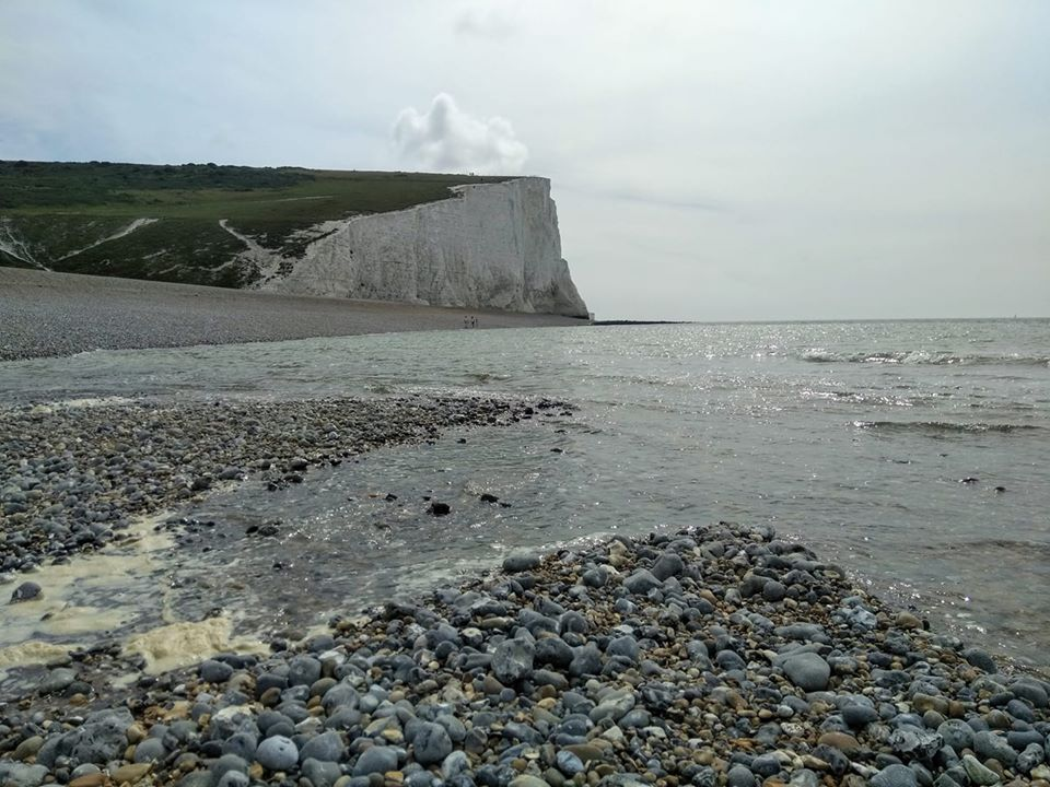 The river opening out on the pebble beach with the white chalk cliffs behind
