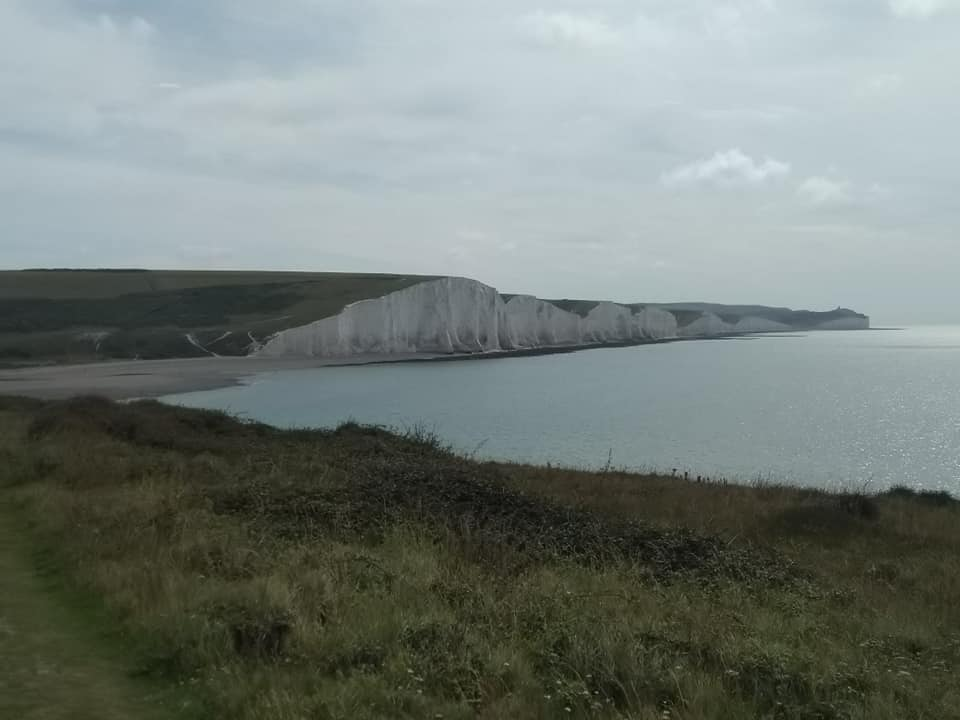 The white chalk cliffs of the Seven Sisters in the distance with sea below