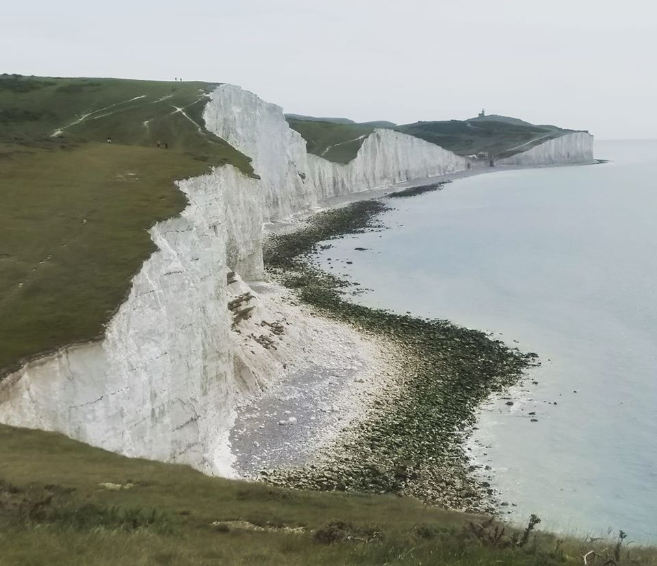 The white chalk cliffs of the Seven Sisters in East Sussex with a pebble beach and blue sea below