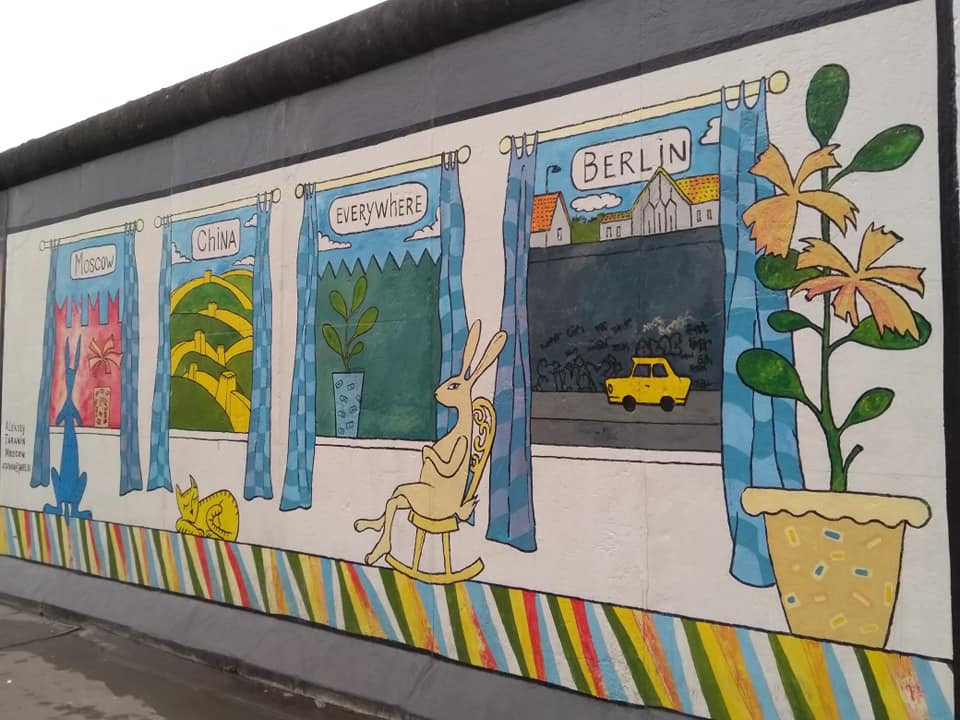 A mural on the Wall at the East Side Gallery depicting animals looking at views of their homes from a window where Berlin's view is just a big grey wall