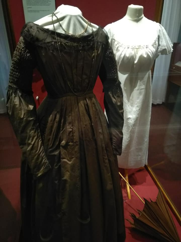 A dark brown dress and a white underdress worn by one of the sisters