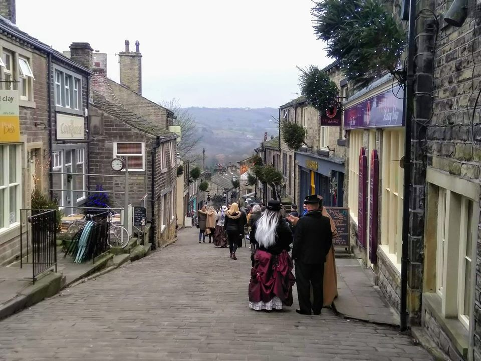 A street in Haworth sloping downhill, with the moors ahead and people dressed in steampunk costumes