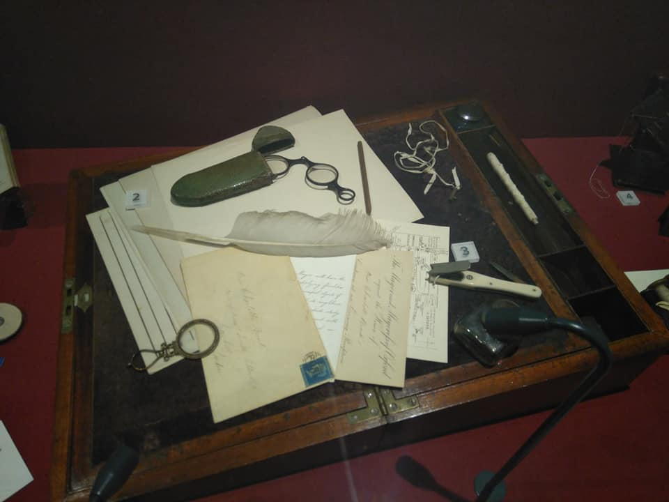 Charlotte's portable writing desk, covered in paper, writing implements and her spectacles