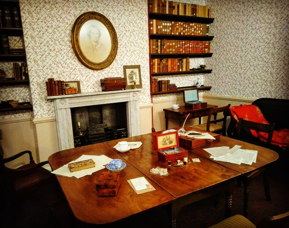 The sitting room in the parsonage in which the sisters used to write; the wooden table is covered in writing implements