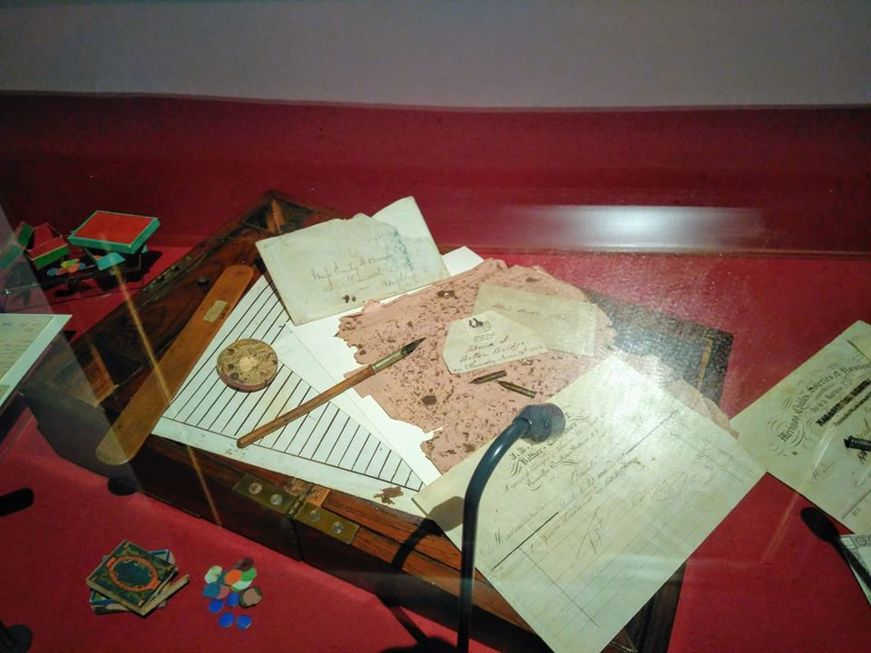 A writing desk covered in paper and writing implements