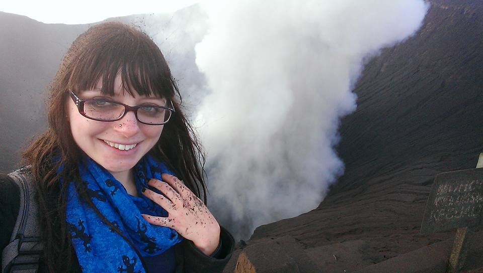 Rachel standing on top of a volcano with behind her and black ash on her face, clothes and glasses