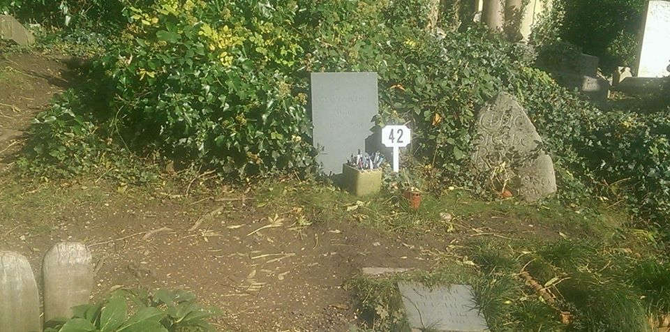 Douglas Adams' gravestone with pens in front of it