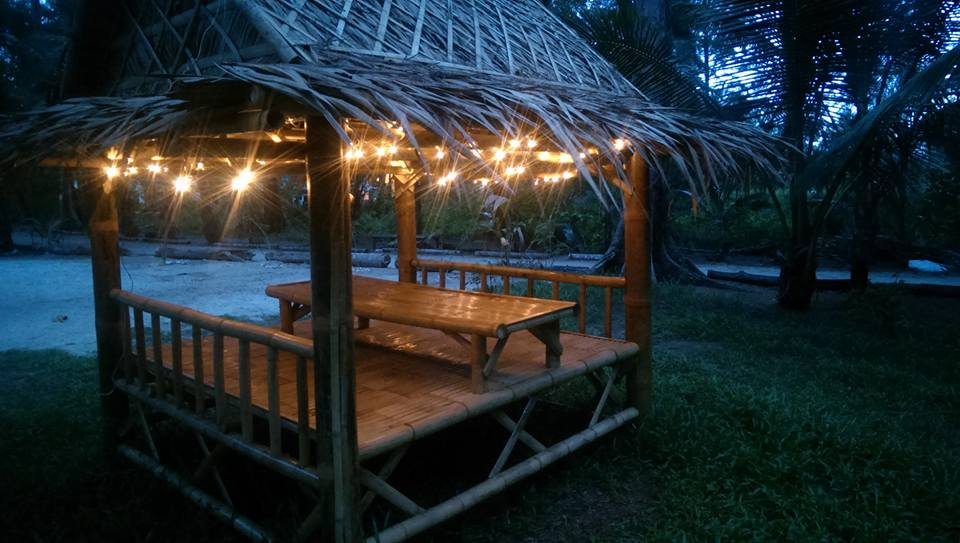 An outdoor bamboo seating area with fairylights