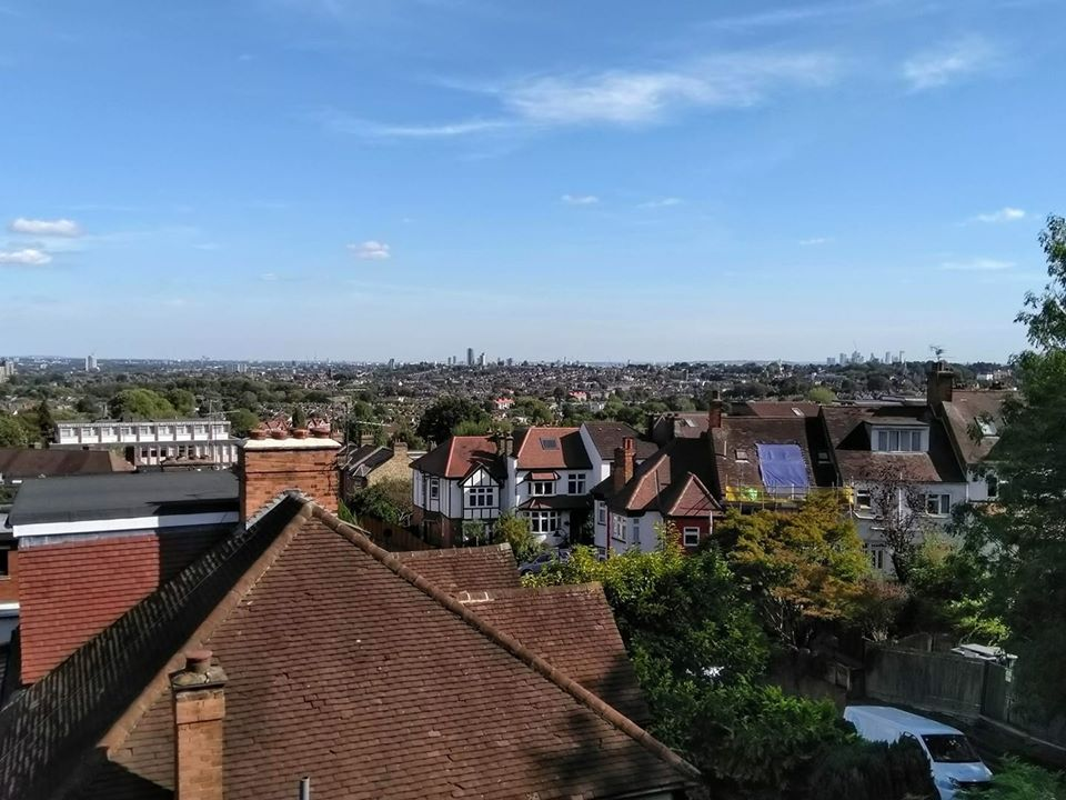 The London city skyline in the distance with rooves of houses in front