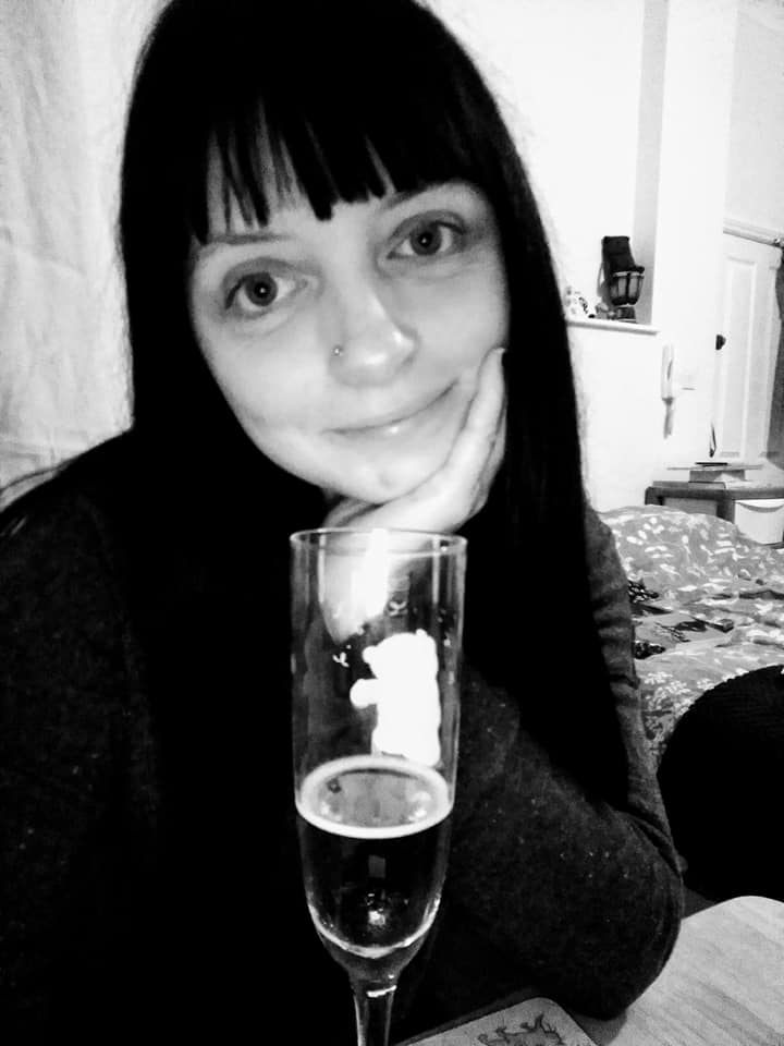 Rachel with a glass of prosecco in black and white