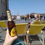 Woman's hand holding a beer up in front of yellow deckchairs on a hill overlooking Brussels city centre